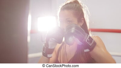 Powerful female boxer knocks punching bag in boxing club -...