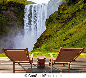 Magnificent famous waterfall Skógafoss, Iceland. A powerful jet Skógar river falls from large glacier. On stony ground in front of the waterfall are two wooden deck chairs