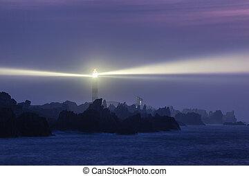 Powerful lighthouse illuminated at night, Ushant island, France