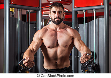 Powerful man with muscular build is training in the gym