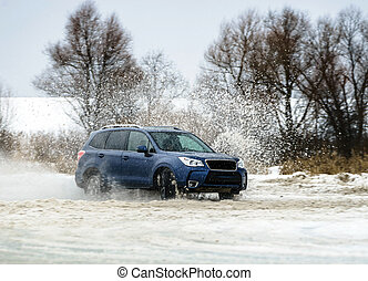 Powerful offroader car sliding by lake ice on winter sport trace