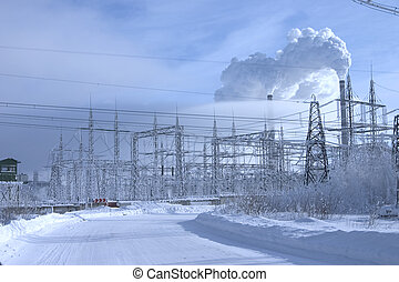 Powerful power station costing in an environment of snowdrifts on a background of the blue sky