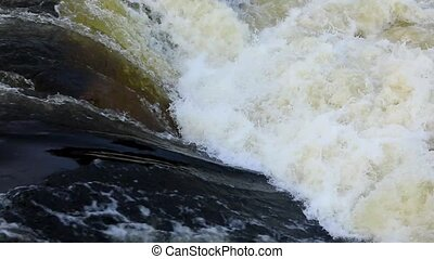 Raging clean fresh mountain river water flowing between rocks in slow notion. Close-up view of powerful flow of mountain river. The poetry of nature