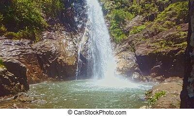 Powerful Waterfall Falls in Deep Pond among Big Rocks