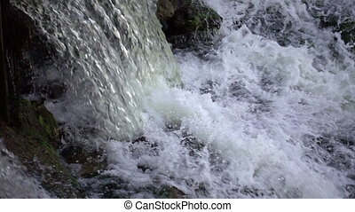 Powerful waterfall in slow motion. Water flows and falls...