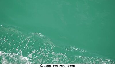 Powerful waves huge stream of deep blue water with white foam rising up in slow motion.