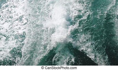 Powerful waves pulled out from fast moving boat, a huge stream of deep blue water with white foam rising up. slow motion.