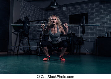 Powerful woman athlete doing squats with heavy weights. cross-training