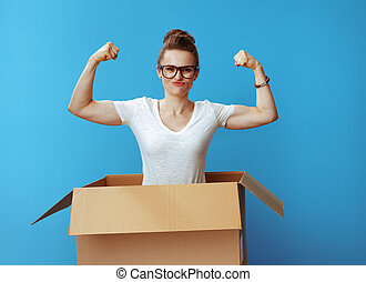 powerful young woman showing biceps in cardboard box on blue