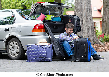 Powerless father next to car trunk, horizontal