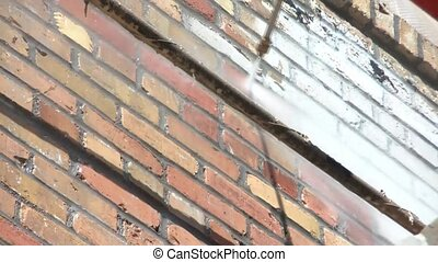 Clip of brick being power washed in sun with high pressure water pulling off white residue after being treated with substance.