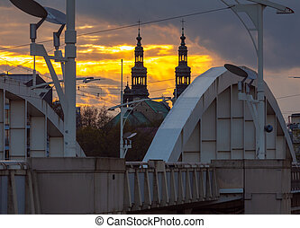 Poznan. The bridge of St. Roch and the church bell tower at sunset.
