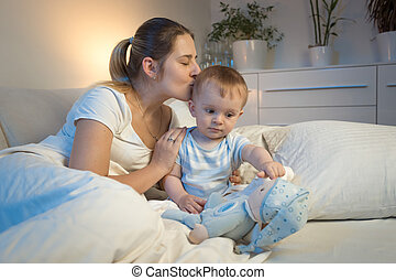 Pportrait of young mother kissing her baby boy before going to sleep at night