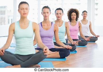prålig, unga kvinnor, in, meditation, pose, med, ögon slöt, hos, a, lysande, fitness, studio