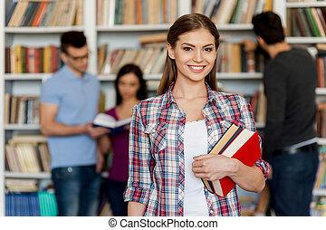 prêt, pour, sien, final, exam., beau, jeune femme, tenue, livres, dans, elle, main, et, sourire, appareil-photo, quoique, trois, autre, gens, tenir, elle, et, près, les, étagère