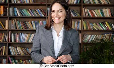 PR manager poses for new library advertisement waving hands and smiling happily standing against different books on brown wooden racks