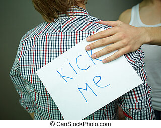 Guy being unaware of a ?Kick me? sign attached to his back