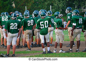Practice lineup - Teenagers on a football team wait for ...