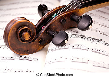 The dusty scroll of an old violin rests in the middle of a musical score. Only one line of music is in focus.