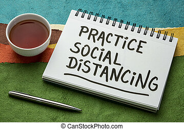 practice social distancing advice or reminder - handwriting in a spiral art sketchbook with a cup of tea against abstract landscape, infection control during covid-19 virus pandemic