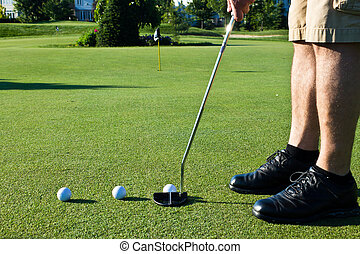 Practicing golf putting with several balls