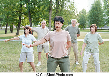 Practicing qigong in park - Mature brunette instructor ...