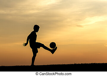 Practicing soccer at sunset.