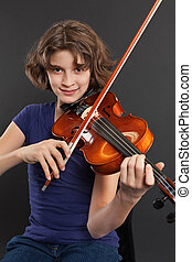 Photo of a young girl practicing the violin over a dark background.