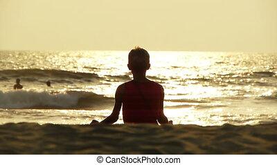 Practicing yoga on Goa beach at sunset