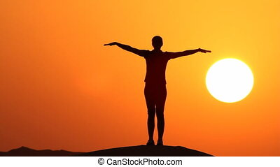 woman practicing yoga in sunset with large sun in the background