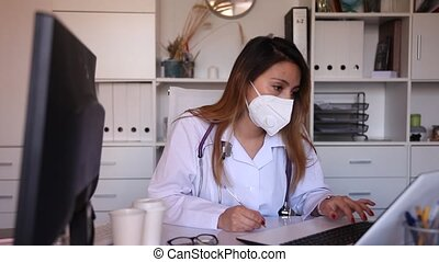 Practicioner peruvian woman in medical mask is working at laptop in clinic