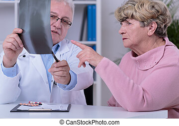 Practitioner analyzing chest x-ray - Elder practitioner...