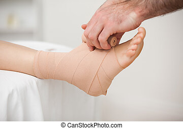Practitioner bandaging an ankle in a medical room