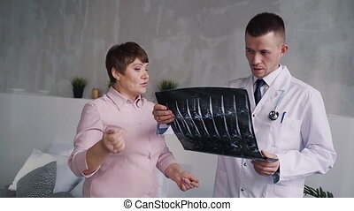 Young, concentrated, focused and serious doctor speaking with matured woman about her x-ray picture. They standing inside bright light room in modern flat room and holding in hands radiological shot