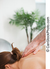 Practitioner massaging the top of back of his patient