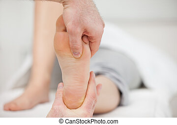 Practitioner placing his thumb on a foot in a medical room