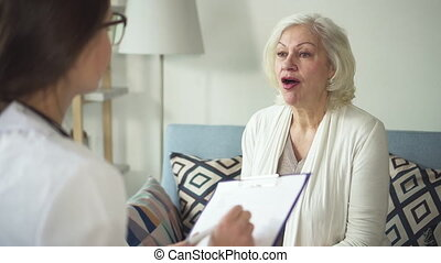 Practitioner talking with sick old lady at her house