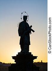 Prague, Czech Republic. Statuette in Charles Bridge at sunrise.