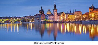 Panoramic image of Prague riverside and Charles Bridge, with reflection of the city in Vltava River.