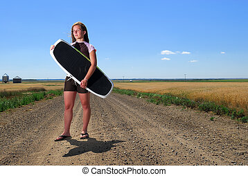 Prairie Girl Wake Boarder - A pretty young woman on dirt...