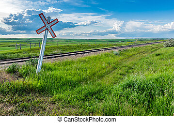 Prairie railway crossing sign and tracks with storm clouds on the horizon in Saskatchewan, Canada