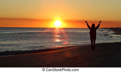 Praise At Sunset - Woman raises her hands in the air to...