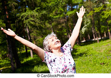 Praise - Portrait of aged woman with her arms raised in ...