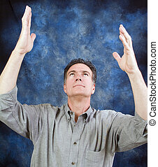 Praise the Lord - A man looking upward with his hands held...