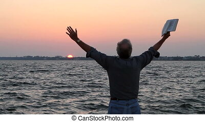 Praise With Bible Sunset - Man holds his arms up with a...