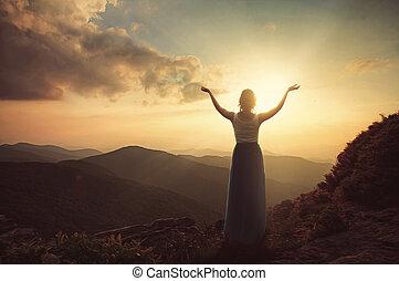 Praising at dusk - A woman praising at dusk on the mountain