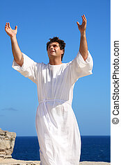A man dressed in white robe with hands raised in spiritual devotion, praise or happiness.