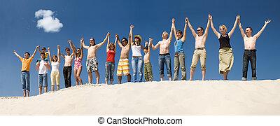 Praising - Image of many friends standing on sandy beach ...