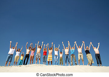 Praising - Image of many friends standing on sandy beach...