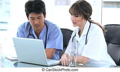 praticiens, ordinateur portable, ensemble, conversation, devant, sérieux
